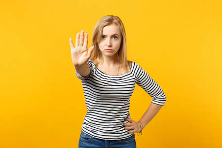 Portrait of serious young woman in striped clothes showing stop gesture with palm isolated on yellow orange wall background in studio. People sincere emotions lifestyle concept. Mock up copy space