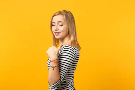 Side view of smiling young woman in striped clothes pointing thumb aside behind her back isolated on yellow orange background in studio. People sincere emotions lifestyle concept. Mock up copy space 免版税图像
