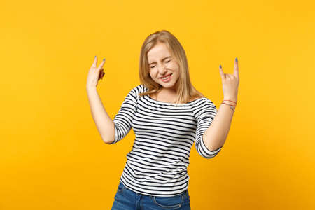 Crazy young woman keeping eyes closed, showing horns up gesture, depicting heavy metal rock sign isolated on yellow orange background. People sincere emotions, lifestyle concept. Mock up copy space Фото со стока