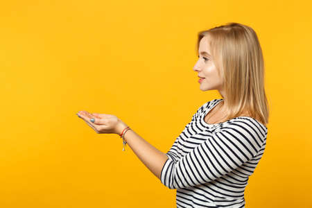 Side view of pretty young woman in striped clothes holding something in hands palms isolated on yellow orange wall background in studio. People sincere emotions, lifestyle concept. Mock up copy space