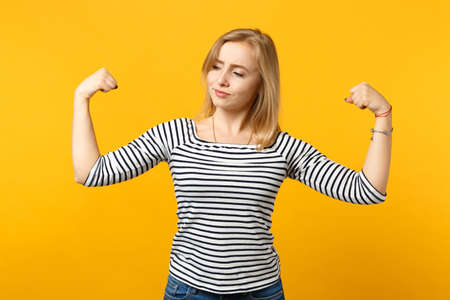 Portrait of strong young woman in striped clothes looking aside, showing biceps, muscles isolated on yellow orange background in studio. People sincere emotions, lifestyle concept. Mock up copy space