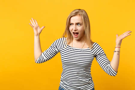 Irritated perplexed young woman in striped clothes looking aside, spreading hands, screaming isolated on yellow orange wall background. People sincere emotions, lifestyle concept. Mock up copy space 写真素材