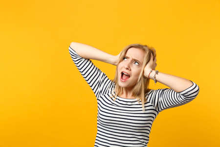 Amazed excited young woman in striped clothes keeping mouth open, looking up putting hands on head isolated on yellow orange background. People sincere emotions, lifestyle concept. Mock up copy space 写真素材