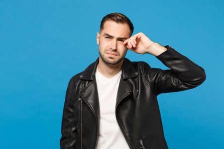 Young sad frustrated worried unshaven man in black jacket white t-shirt looking camera isolated on blue wall background studio portrait. People sincere emotions lifestyle concept. Mock up copy space 写真素材