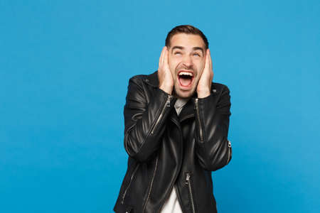 Handsome stylish young unshaven man in black leather jacket white t-shirt looking camera isolated on blue background studio portrait. People sincere emotions lifestyle concept. Mock up copy space Stok Fotoğraf