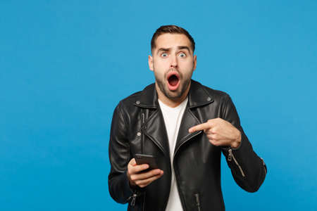 Handsome overjoyed excited young unshaven man in black leather jacket white t-shirt using mobile phone isolated on blue wall background studio portrait. People lifestyle concept. Mock up copy space Imagens