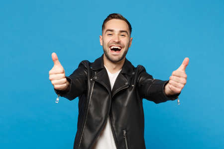 Handsome stylish young bearded man in black leather jacket white t-shirt looking camera isolated on blue wall background studio portrait. People sincere emotions lifestyle concept. Mock up copy space
