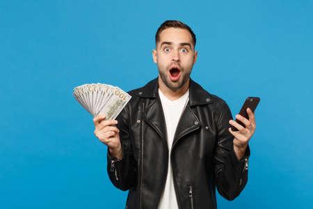 Junger Mann in schwarzer Lederjacke, weißem T-Shirt, das einen Fan von Bargeld in Dollar-Banknoten hält, Handy isoliert auf blauem Wandhintergrund Studioportrait. Menschen Lifestyle-Konzept. Mock-up-Kopierraum