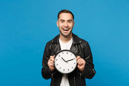 Handsome stylish young unshaven man in black leather jacket white t-shirt holding round clock isolated on blue wall background studio portrait. People lifestyle concept. Hurry up. Mock up copy space Foto de archivo