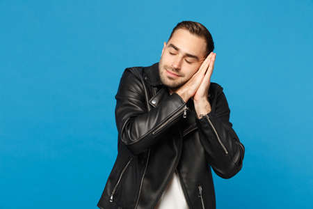 Young unshaven man in black jacket white t-shirt sleep with folded hands under cheek isolated on blue wall background studio portrait. People sincere emotions lifestyle concept. Mock up copy space