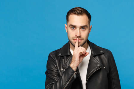 Stylish bearded man in black leather jacket white t-shirt say hush be quiet with finger on lips shhh gesture isolated on blue wall background studio portrait. People sincere emotions concept. Mock up