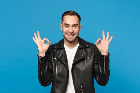 Handsome stylish young bearded man in black leather jacket white t-shirt looking camera isolated on blue wall background studio portrait. People sincere emotions lifestyle concept. Mock up copy space 写真素材