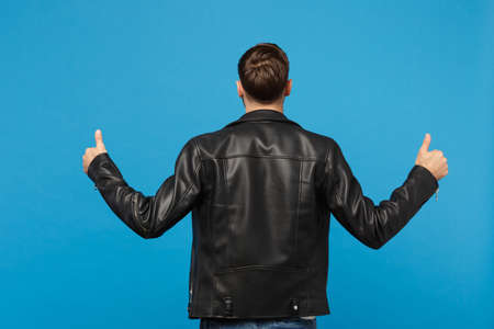 Handsome stylish young unshaven man in black leather jacket white t-shirt looking camera isolated on blue background studio portrait. People sincere emotions lifestyle concept. Mock up copy space Stock Photo