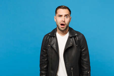Young sad frustrated worried unshaven man in black jacket white t-shirt looking camera isolated on blue wall background studio portrait. People sincere emotions lifestyle concept. Mock up copy space Stok Fotoğraf