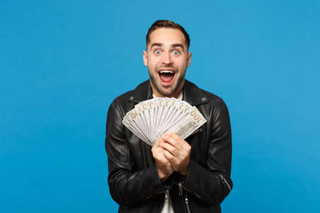 Young unshaven man in black leather jacket white t-shirt holding fan of cash money in dollar banknotes isolated on blue wall background studio portrait. People lifestyle concept. Mock up copy space Stock Photo