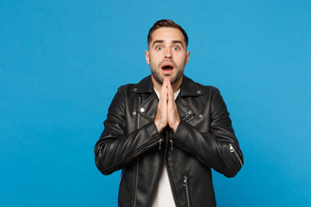 Stylish bearded man in black leather jacket white t-shirt looking camera hold pray hands isolated on blue background studio portrait. People sincere emotions lifestyle concept. Mock up copy space