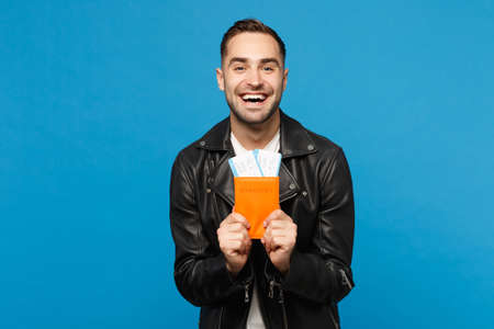 Young happy unshaven man in black jacket white t-shirt hold in hand passport tickets isolated on blue background. Passenger traveling abroad getaway. Air flight journey concept Mock up copy space