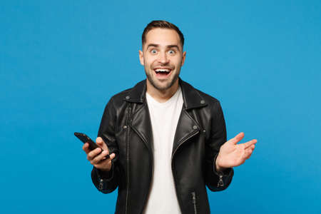 Handsome overjoyed excited young unshaven man in black leather jacket white t-shirt using mobile phone isolated on blue wall background studio portrait. People lifestyle concept. Mock up copy space Reklamní fotografie