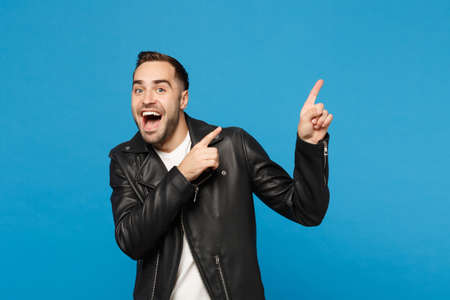 Handsome stylish young unshaven man in black jacket white t-shirt showing on workspace isolated on blue wall background studio portrait. People sincere emotions lifestyle concept. Mock up copy space