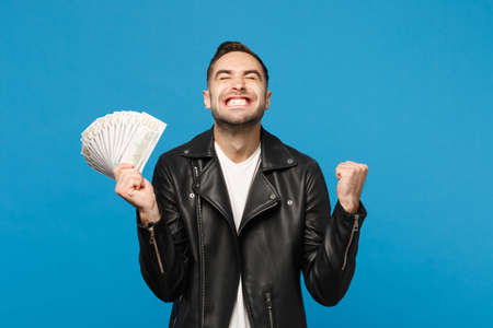 Young unshaven man in black leather jacket white t-shirt holding fan of cash money in dollar banknotes isolated on blue wall background studio portrait. People lifestyle concept. Mock up copy space Фото со стока