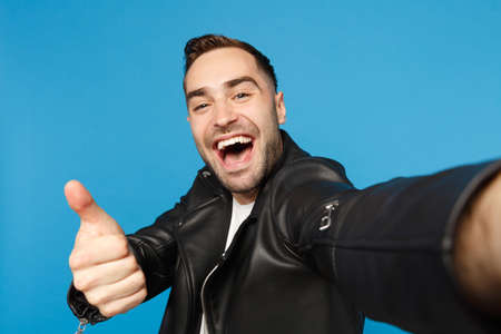Close up selfie of stylish young unshaven man in black leather jacket white t-shirt looking camera isolated on blue background studio portrait. People sincere emotions concept. Mock up copy space 写真素材