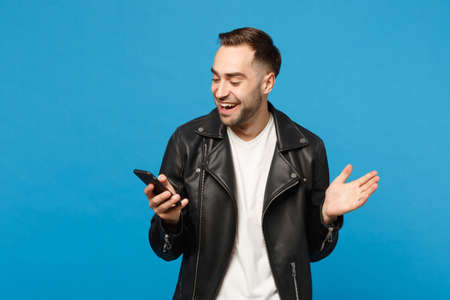 Handsome overjoyed excited young unshaven man in black leather jacket white t-shirt using mobile phone isolated on blue wall background studio portrait. People lifestyle concept. Mock up copy space Banco de Imagens