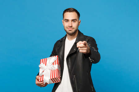 Handsome stylish young bearded man in black leather jacket white t-shirt hold gift box isolated on blue wall background studio portrait. People sincere emotions lifestyle concept. Mock up copy space