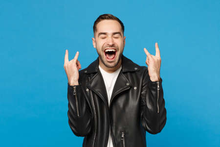Handsome stylish young unshaven man in black leather jacket white t-shirt looking camera isolated on blue background studio portrait. People sincere emotions lifestyle concept. Mock up copy space