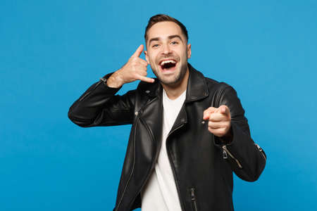 Young unshaven man in black jacket white t-shirt looking camera doing phone gesture like says call me back isolated on blue background studio portrait. People lifestyle concept Mock up copy space 스톡 콘텐츠