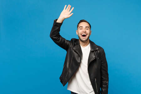 Handsome stylish young man in black jacket white t-shirt waving and greeting with hand as notices someone isolated on blue background studio portrait. People lifestyle concept. Mock up copy space