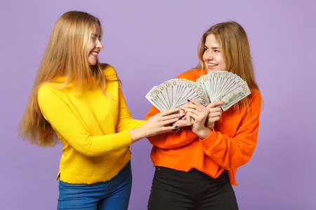 Two cheerful blonde twins sisters girls in colorful clothes holding fan of money in dollar banknotes cash money isolated on violet blue background. People family lifestyle concept. Mock up copy space