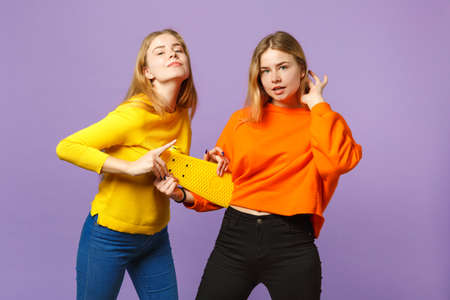 Two pretty young blonde twins sisters girls in vivid colorful clothes holding yellow skateboard isolated on pastel violet blue wall background. People family lifestyle concept. Mock up copy space