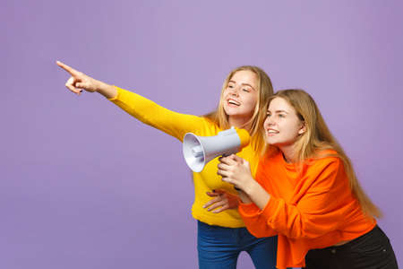 Two young blonde twins sisters girls in colorful clothes pointing index finger aside scream on megaphone isolated on pastel violet blue background. People family lifestyle concept. Mock up copy space