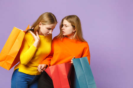 Two beautiful young blonde twins sisters girls in vivid clothes hold package bag with purchases after shopping isolated on violet blue background. People family lifestyle concept. Mock up copy space