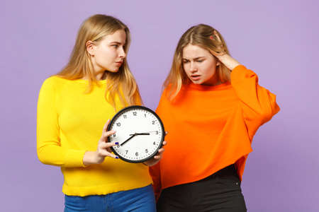 Two puzzled young blonde twins sisters girls in vivid colorful clothes hold round clock isolated on pastel violet blue wall background in studio. People family lifestyle concept. Mock up copy space