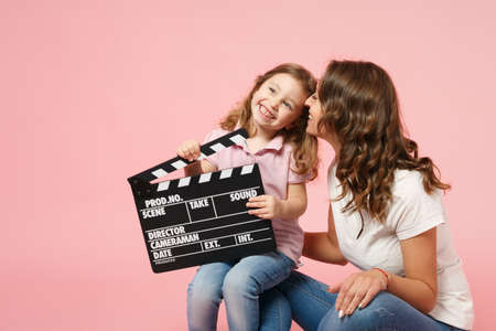 Woman in light clothes hold clapperboard, child baby girl. Mother, little kid daughter isolated on pastel pink wall background, studio portrait. Mothers Day, love family parenthood childhood concept 版權商用圖片