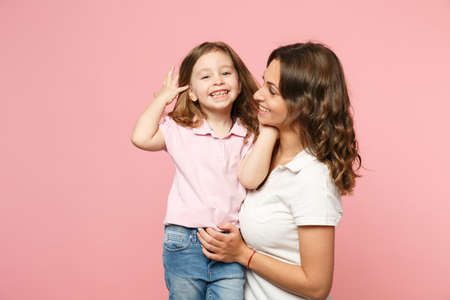 Woman in light clothes have fun with cute child baby girl. Mother, little kid daughter isolated on pastel pink wall background, studio portrait. Mother's Day love family, parenthood childhood concept Stock Photo - 122147924
