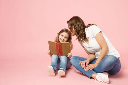 Woman in light clothes have fun read book with child baby girl. Mother, little kid daughter isolated on pastel pink background, studio portrait. Mother's Day, love family parenthood childhood concept