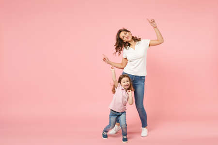 Woman in light clothes have fun with cute child baby girl. Mother, little kid daughter isolated on pastel pink wall background, studio portrait. Mother's Day love family, parenthood childhood concept Stockfoto