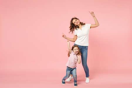 Vrouw in lichte kleding veel plezier met schattig kind babymeisje. Moeder, klein kind dochter geïsoleerd op pastel roze muur achtergrond, studio portret. Moederdag liefde familie, ouderschap kindertijd concept
