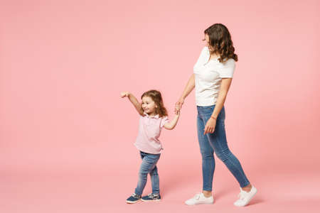 Woman in light clothes have fun with cute child baby girl. Mother, little kid daughter isolated on pastel pink wall background, studio portrait. Mother's Day love family, parenthood childhood concept Stock Photo - 122169227