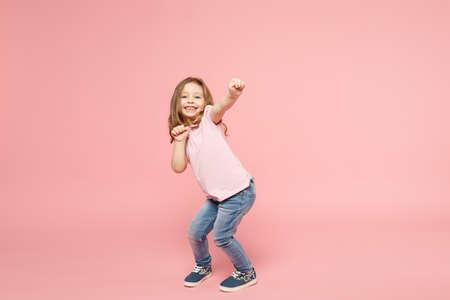 Petit enfant mignon bébé fille 3-4 ans portant des vêtements légers dansant isolé sur fond de mur rose pastel, portrait en studio pour enfants. Fête des mères, famille d'amour, concept d'enfance parentale