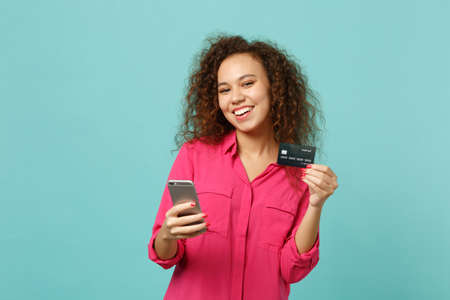 Smiling african girl in pink casual clothes using mobile phone, holding credit bank card isolated on blue turquoise background in studio. People sincere emotions lifestyle concept. Mock up copy space 写真素材