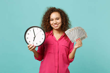 Smiling african girl in pink clothes hold round clock fan of money in dollar banknotes cash money isolated on blue turquoise background. People sincere emotions, lifestyle concept. Mock up copy space
