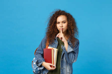 Young african american girl teen student in denim clothes, backpack hold books isolated on blue background studio portrait. Education in high school university college concept. Mock up copy space Stok Fotoğraf