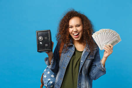 Young african american girl teen student in denim clothes, backpack hold safe isolated on blue wall background studio portrait. Education in high school university college concept. Mock up copy space
