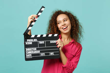 Portrait of funny african girl in casual clothes holding classic black film making clapperboard isolated on blue turquoise background. People sincere emotions lifestyle concept. Mock up copy space