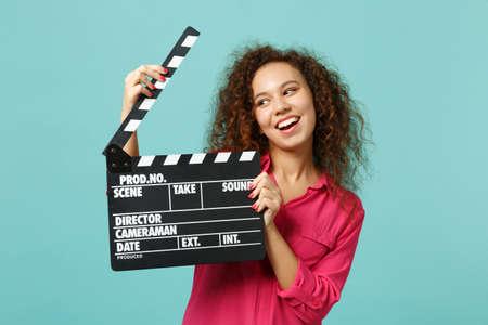 Retrato de niña africana divertida en ropa casual sosteniendo claqueta de cine negro clásico aislado sobre fondo azul turquesa. Concepto de estilo de vida de emociones sinceras de personas. Simulacros de espacio de copia Foto de archivo