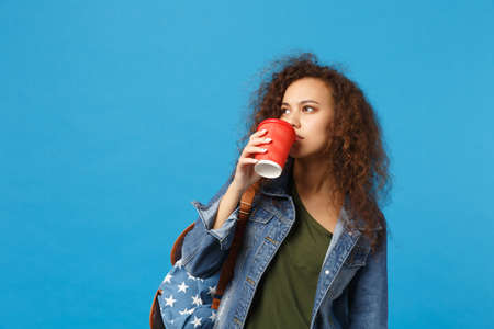 Young african american girl teen student in denim clothes, backpack hold paper cup isolated on blue background studio portrait. Education in high school university college concept. Mock up copy space