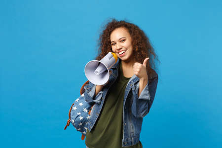 Young african american girl teen student in denim clothes, backpack hold megaphone isolated on blue background studio portrait. Education in high school university college concept. Mock up copy space